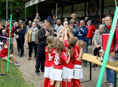 Die Mädchen freuen sich über ihren Pokal.